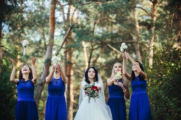 Braut und brautjungfern werfen blumensträuße