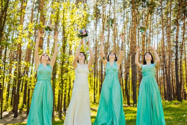 Braut und brautjungfern werfen hochzeitssträuße.