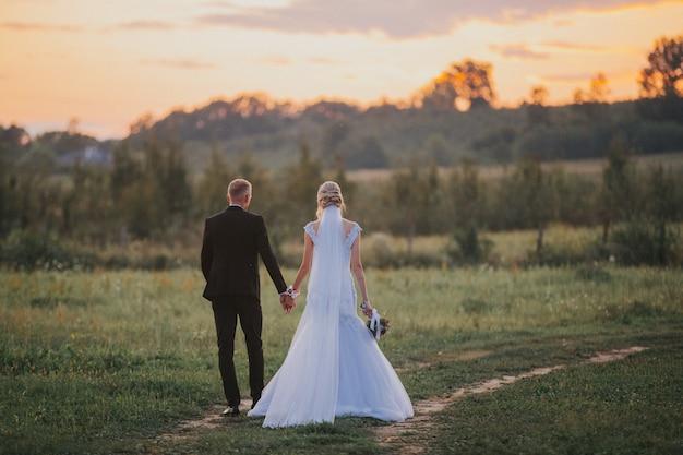 Braut und der bräutigam, die hände nach der hochzeitszeremonie in einem feld bei sonnenuntergang halten