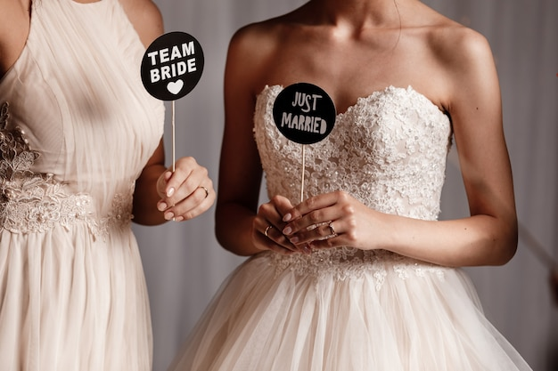 Braut und ihre brautjungfer, die zubehör für die hochzeitsfotoaufnahme halten. hochzeit.