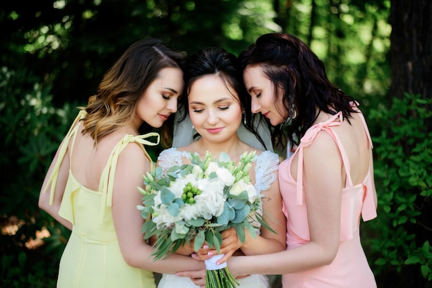 Braut und ihre hübschen brautjungfern in den rosa und gelben kleidern werfen im hellen park auf