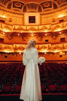 Braut warte einen bräutigam in einer alten halle des theaters