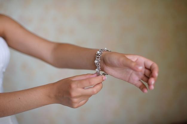Braut zieht armband an