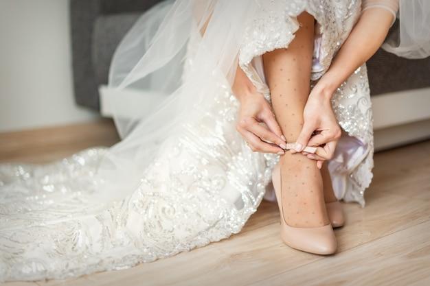 Braut zieht hochzeitsschuhe an