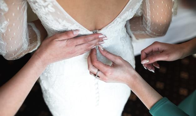 Braut zieht ihr weißes hochzeitskleid an