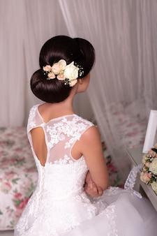 Braut zurück mit hochzeitsfrisur, kleid und blumen
