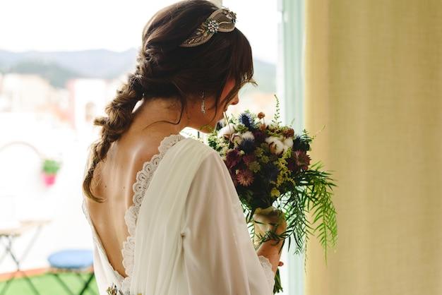 Braut zurück mit ihrem hochzeitskleid, das ihren blumenstrauß hält.