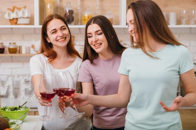 Brautdusche. spaß und feier. glückliche junge frauen, die freund gratulieren. rotweingläser klirren.