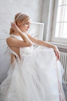 Brautfrau in einem leichten sommerhochzeitskleid, das am fenster sitzt und auf die hochzeitszeremonie wartet. mädchen mit perfektem haar und schönem make-up