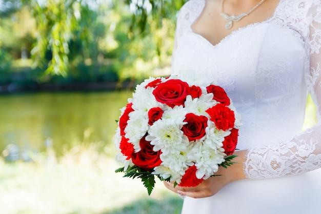 Brauthände, die brautblumenstrauß von roten rosen und weißen chrysanthemenabschluß hochhalten
