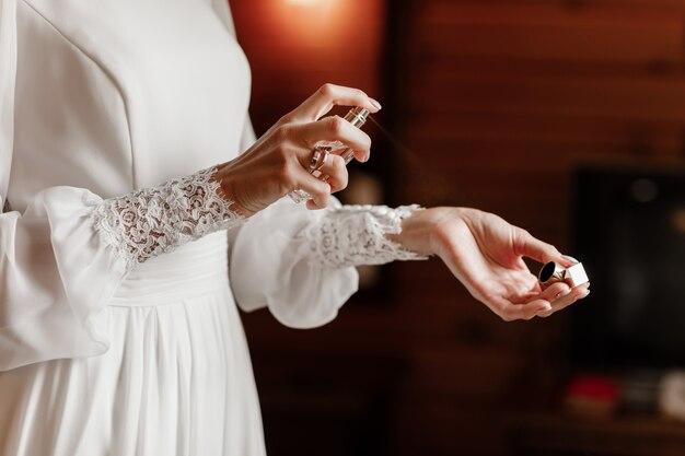Brauthände, die parfüm auf ihrem handgelenk anwenden
