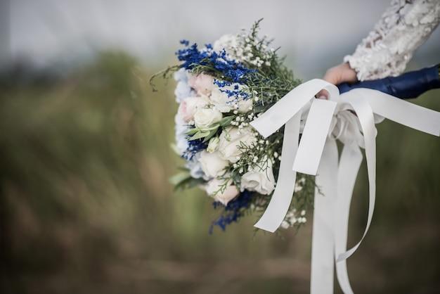 Brauthand, die blume am hochzeitstag hält
