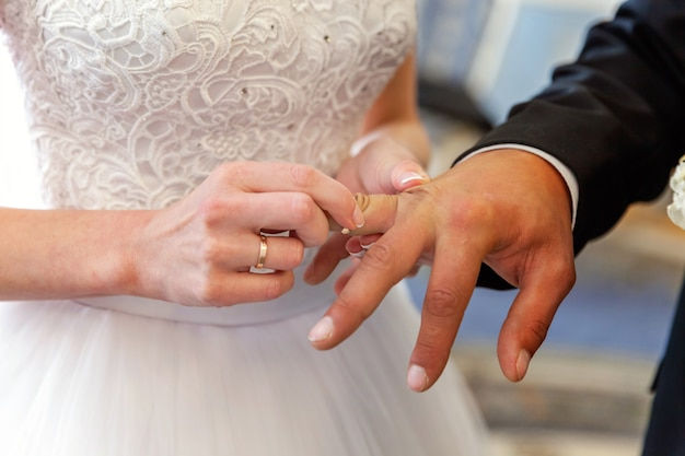 Brauthand, die ehering auf bräutigamfinger setzt