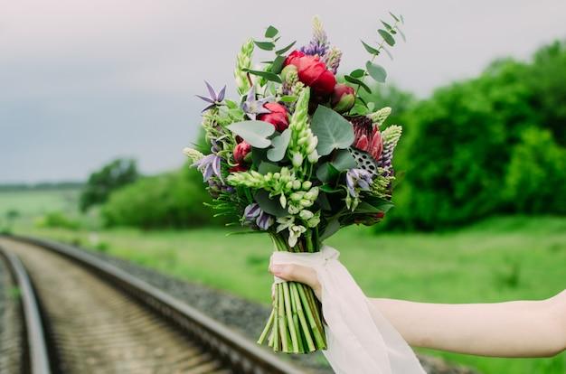 Brauthand mit hochzeitsblumenstrauß in ihren händen.