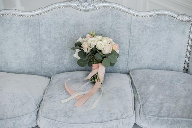 Brauthochzeitsstrauß auf dem bett