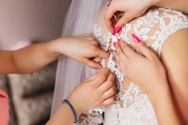 Brautjungfer bereitet braut für den hochzeitstag vor. weißes kleid befestigen