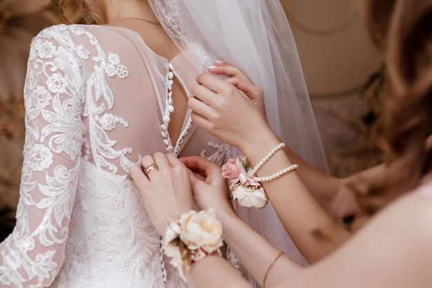 Brautjungfer, die brautkorsett hilft und ihr kleid erhält