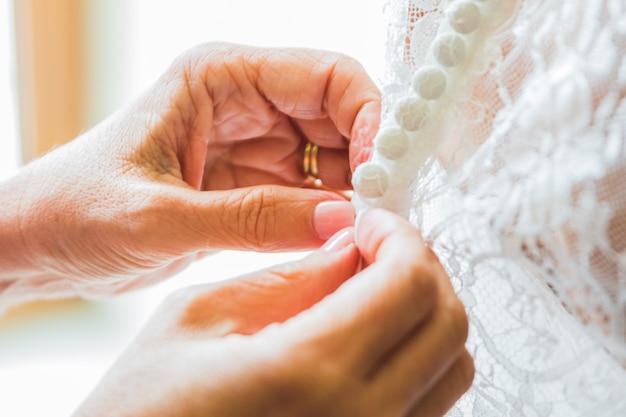 Brautjungfer, die der braut hilft, das korsett zu befestigen und ihr kleid zu bekommen