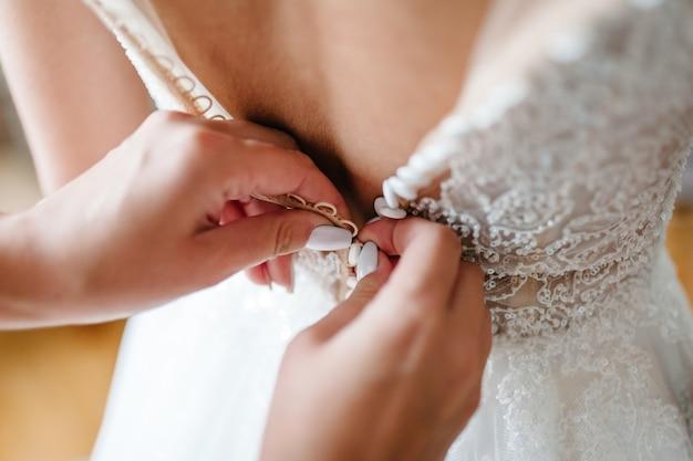 Brautjungfer, die der braut hilft, knöpfe am korsett zu befestigen und ihr kleid zu bekommen, bereitet die braut am morgen auf den hochzeitstag vor.