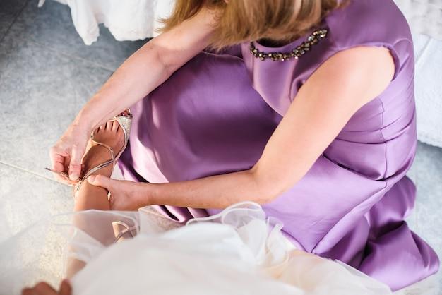 Brautjungfer, die junger braut hilft, die schuhe vor der hochzeitszeremonie anzuziehen.