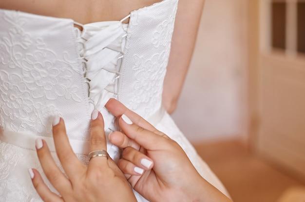 Brautjungfer hilft braut, sich morgens anzuziehen