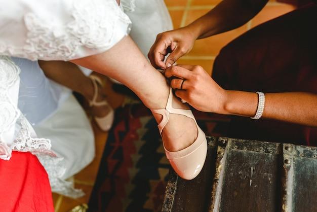 Brautjungfer hilft der braut, ihre schuhe anzuziehen.