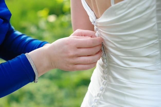 Brautjungfer hilft der braut, sich am hochzeitstag anzuziehen