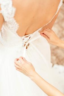 Brautjungfer hilft der braut, sich anzuziehen