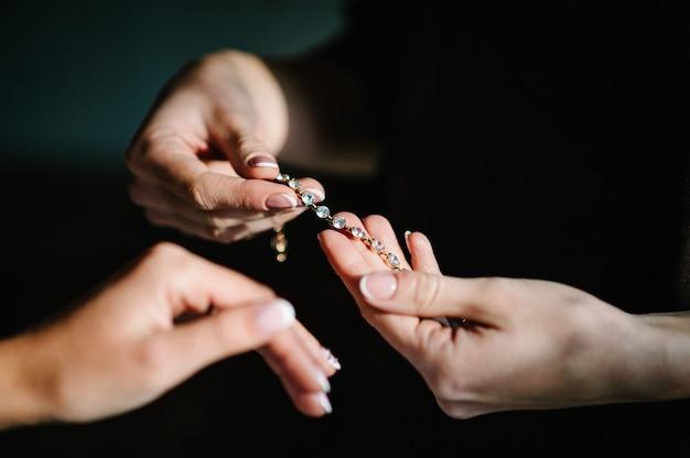 Brautjungfer hilft, ein armband für die braut an seinen arm zu legen. braut zieht schmuck an, konzentriert sich auf armband. brautvorbereitung für die hochzeitszeremonie.
