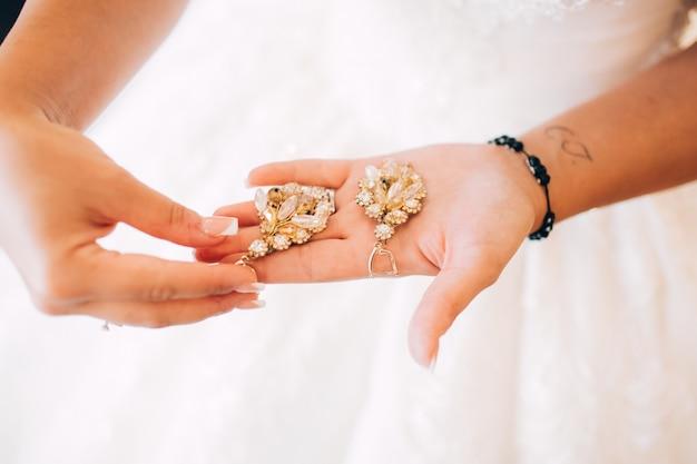 Brautjungfer kleider ohrringe. frau hält einen ohrring. sanfter morgen der braut.