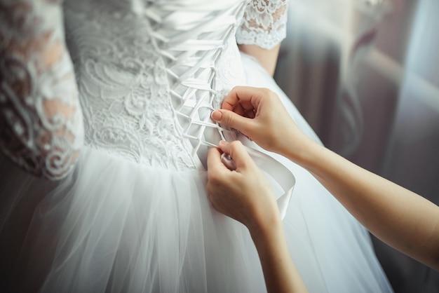Brautjungfer macht bogenknoten auf dem rücken des hochzeitskleides der bräute