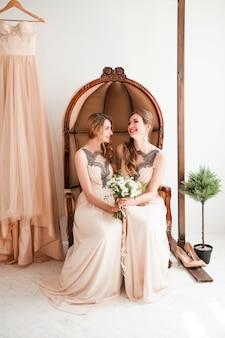 Brautjungfer mit einem hochzeitsstrauß, der in einem weinlesestuhl sitzt