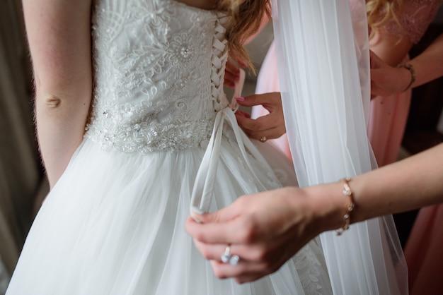 Brautjungfern helfen braut, sich für eine hochzeit bereit zu machen