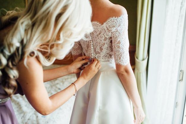 Brautjungfern helfen, ein hochzeitskleid zu tragen