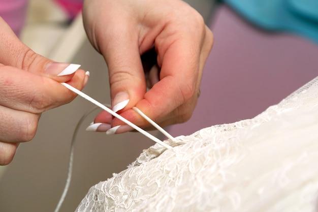 Brautjungfern helfen ihr beim anziehen des hochzeitskleides. schönheit und mode in der damenbekleidung
