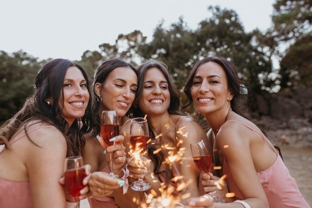 Brautjungfern in hübschen kleidern feiern die hochzeit im freien