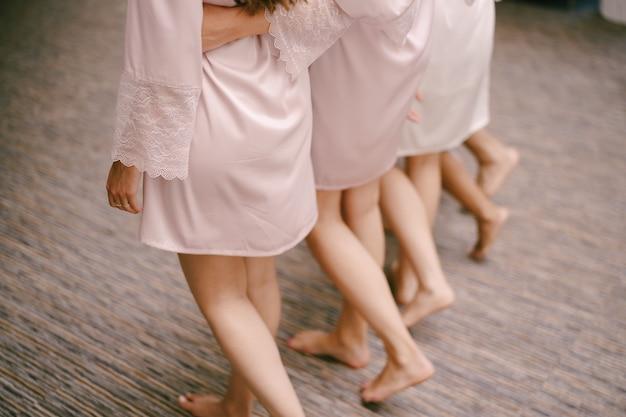 Brautjungfern in roben laufen über den boden