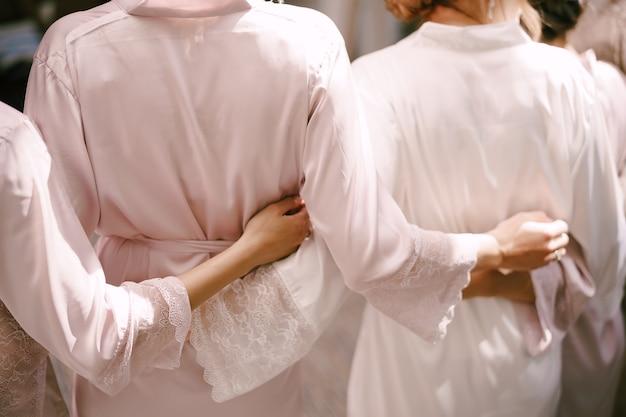 Brautjungfern in roben umarmen sich in der rückansicht