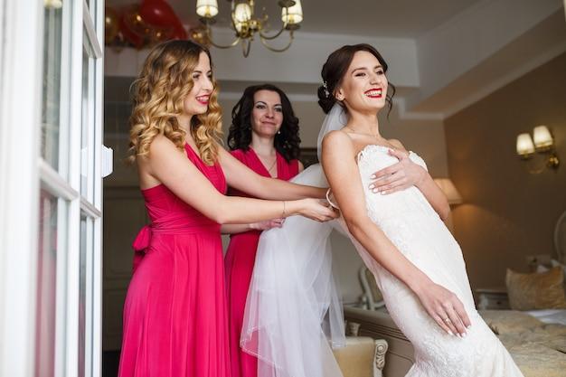 Brautjungfern in rosa kleidern befestigen kleid auf dem rücken der braut