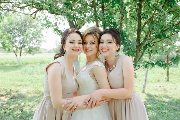 Brautjungfern umarmen die braut im garten