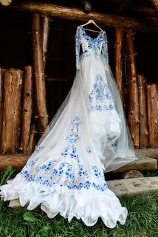 Brautjungfernkleid im stil von gzhel hängt an einem holzbalken in der eingangsöffnung des hauses