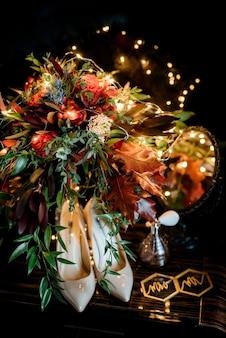 Brautjungfernschuhe mit aksessuarami stehen auf einem braunen tisch