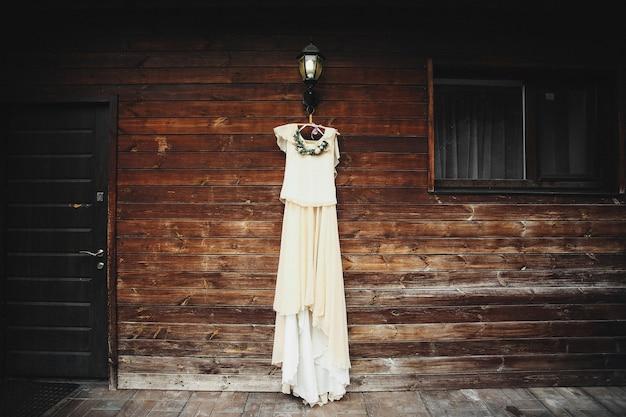 Brautkleid hängt an einer holzwand