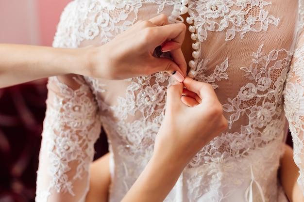 Brautkleid mit muster. brautjungfern befestigen die knöpfe am brautkleid. nahansicht.