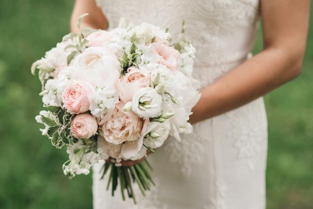 Brautmorgen details. hochzeitsschöner blumenstrauß in den händen der braut, selectoin fokus