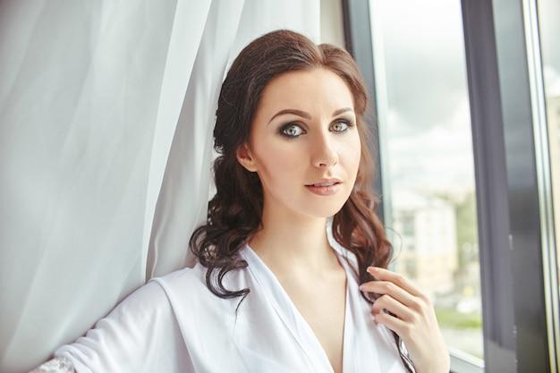 Brautmorgen, ein mädchen in einem seidengewand, das neben dem fenster vor den weißen vorhängen steht. schöne brünette vor der hochzeit