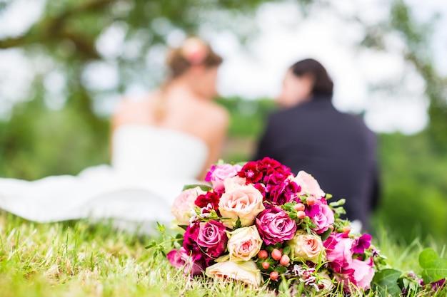 Brautpaar mit dem blumenstrauß, der auf wiese sitzt