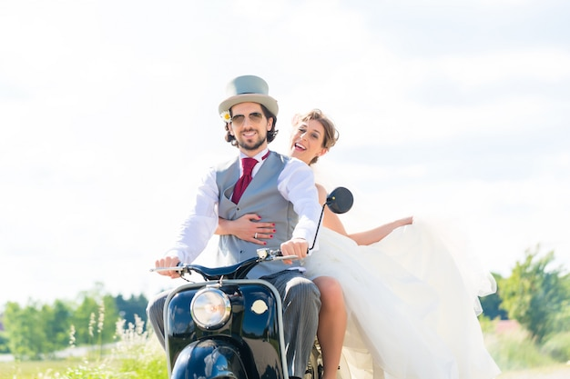Brautpaare, die tragendes kleid und anzug des motorrollers fahren