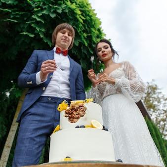 Brautpaare und brautjungfern haben spaß und essen beim hochzeitsbankett zusammen an der frischen luft hochzeitstorte.