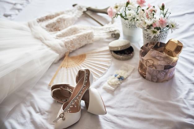 Brautschuhe, kleid, parfüm, blumen und schmuck der stilvollen weißen hochzeit auf weiß